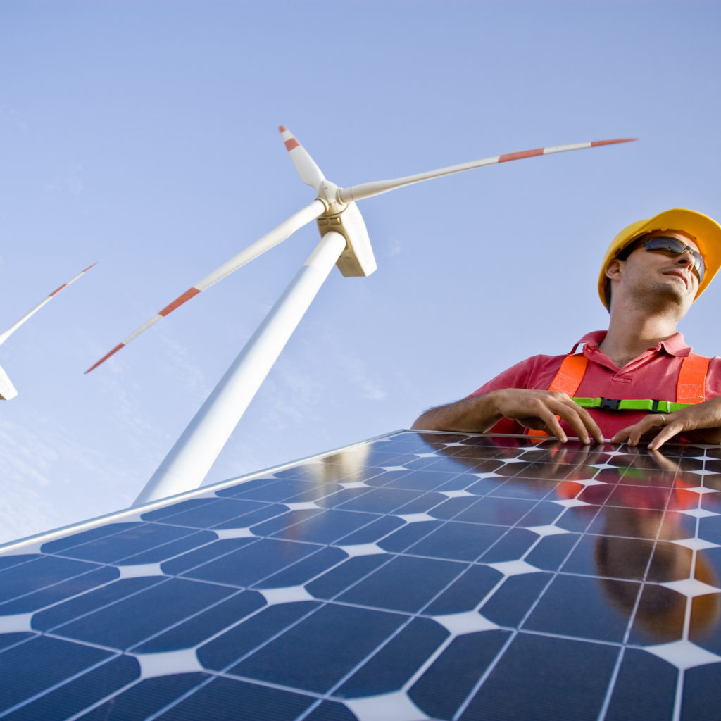 Image of a worker with a photovoltaic panel and having 2 wind turbines in the background to also generate green energy (ISO 100). All my images have been processed in 16 Bits and transfer down to 8 before uploading.
